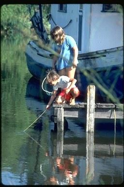 A boy and a woman at the end of a dock, pulling a line from the water and holding a fish net