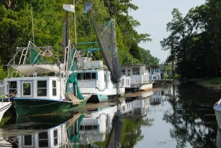 Four shrimp boats out on a bayou waterway