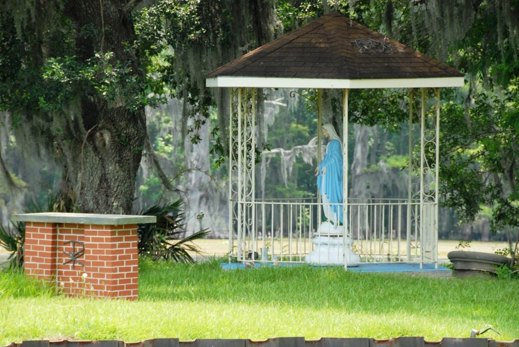 A metal, roofed gazebo with a religious figure inside, and a short brick sign nearby